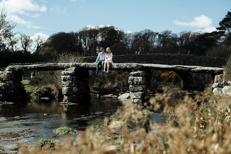 couple sat on a clapper bridge Dartmoor