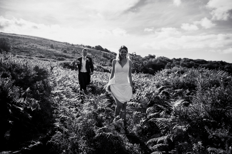bride and groom walking through ferns